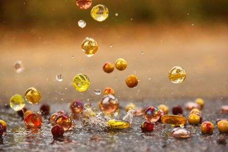 Glass balls in water. Water drops. Multicolored glass balls. Background