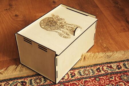 Wooden box on a background of wooden floor and carpet. Handmade box