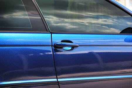 Part of a blue car. Car door close up