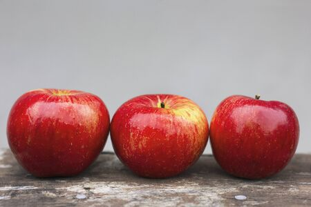 Three red apples on a gray background