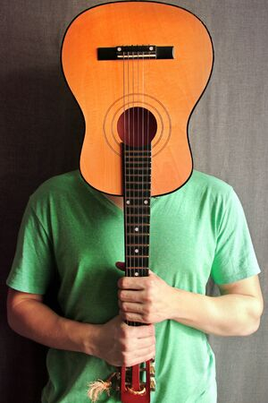 The guy with the guitar. Guitar in the hands of a guy. Abstract photo