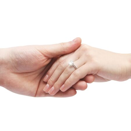 Ring with a stone on her hand. Male hand holds a female hand on a white background. Body parts.