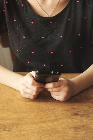 Black phone in the hands of a girl in a black T-shirt