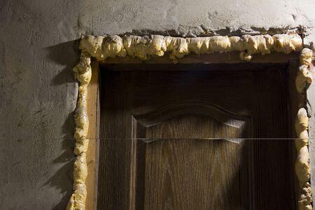 Repair in the house. Doors. Construction foam. Plastered walls