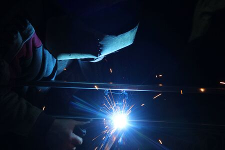 Sparks from welding. A man will weld metal. Фото со стока