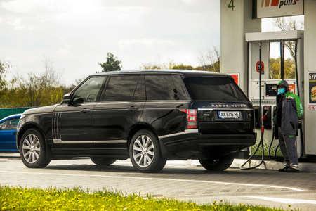 Kiev, Ukraine - April 21, 2020: Range Rover SUV at a fuel station. Petrol. Diesel Masked man 新闻类图片