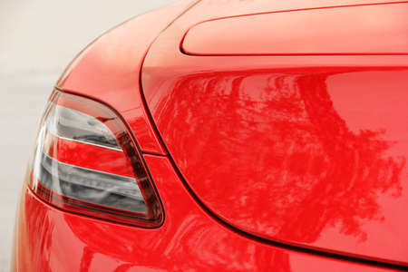 Car headlights. Luxury Headlights. Part of a red car close up. Bumper 免版税图像