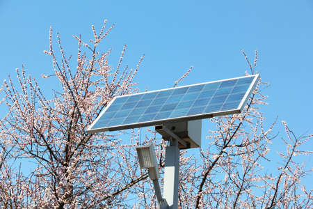 Solar battery against the background of flowering trees and the sky. Solar battery and diode lamp. Spring Standard-Bild