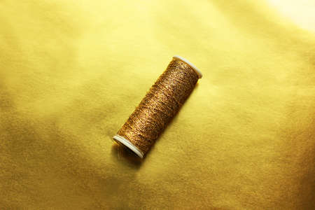 Sewing gold threads on a gold background. Bright shiny threads. Trending color
