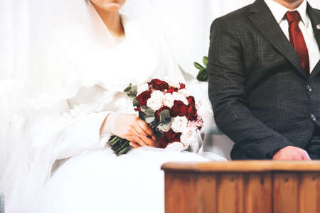 Bride and groom together close up. Bride with a wedding bouquet. Wedding dress and red tie. Wedding