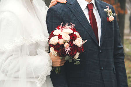 Bride and groom together close up. Bride with a wedding bouquet. Wedding dress and red tie.