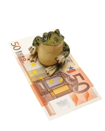Figurine of a frog and money on a white background (isolated).