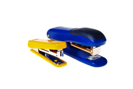 Yellow and blue staplers on a white background close-up (isolated).