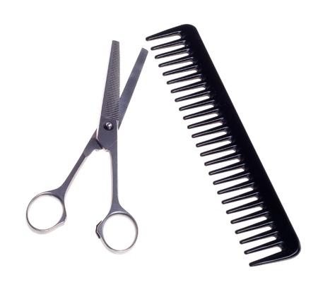 Tijeras de peluquería y peine aislado en un fondo blanco.