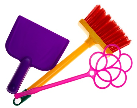 Toy plastic dustpan, carpet beater and broom isolated on a white background. photo