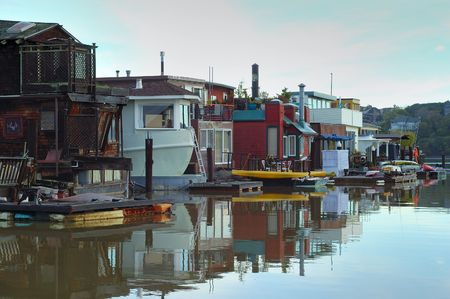 A community on the water in Sausalito, Northern California. Early morning stains the clouds pink, calm waters reflect varied shapes of the houses with boats... 版權商用圖片