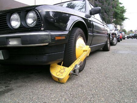 parking violation: Busted: the car was booted for multiple parking violations Stock Photo