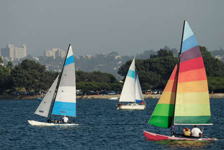 taut: Two yachts and a catamaran are sailing in a Mission Bay, California on a nice summer afternoon.