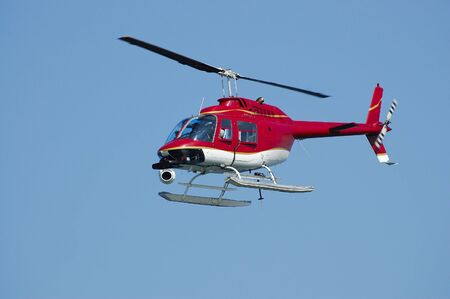 A bright red helicopter with a camera on a Fleet Week Air Show in 2006. A little motion blur on rotor blades