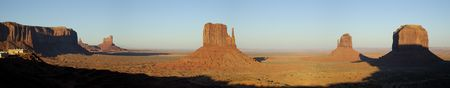 panoramics: A panorama of West and East Mitten Buttes, Merricks Buttes, and a visitor center lit by setting sun. Stock Photo