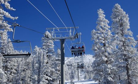 Skiers are riding a ski lift on a skiing resort at Lake Tahoe on a very cold day after a heavy snowstorm. Seats, cables a pillars are covered in frost. photo