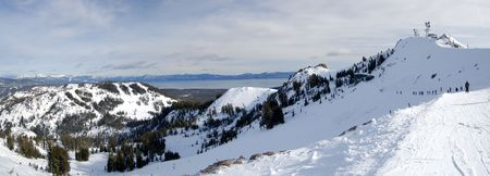Panorama shot of the Lake Tahoe ski resort at Lake Tahoe, California. A line of skiers is snaking towards the slope with communications tower in the background. photo