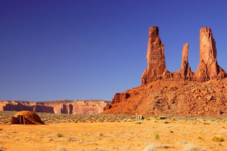 dwelling: Three Sisters mesa in Monument Valley and tradiional indian dwelling with tourist looking inside. Stock Photo