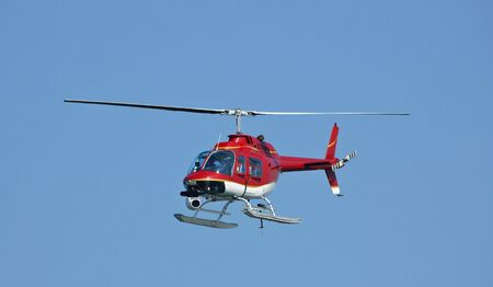 A bright red helicopter with a camera. A little motion blur on rotor blades