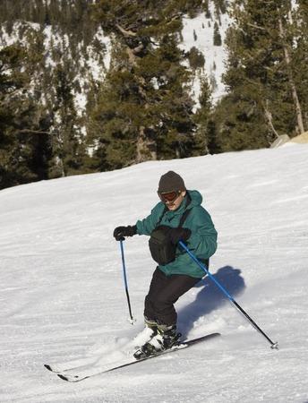 black ski pants: A man with chest pack skiing downhill at lake Tahoe resort, Sierra Nevada, California.