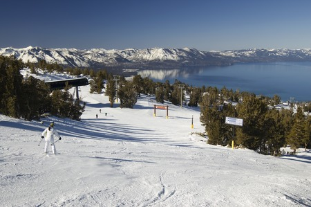 going down: A young inexperienced female skier going down the slope on a lake tahoe ski resort.