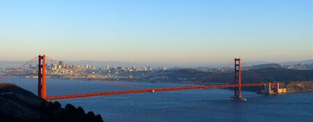 panoramics: A panoramic image of Golden Gate Bridge lit by the setting sun with the San Francisco skyline in the background. Stock Photo