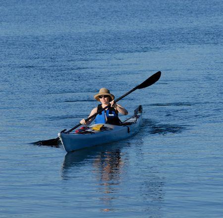 subtropics: Attraente kayaker femmina giovane � canottaggio in acque subtropicali blu profondo del Mission Bay, San Diego, California.  Archivio Fotografico