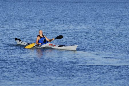 demonstrate: Athletic male kayaker emerges on the surface after paddle float assisted re-entry and roll. Stock Photo