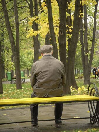 A lonely old man sitting on a bench in a park in Moscow among coloful autumn tres.           Stock Photo