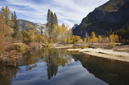 merced: Half Dome is reflected in the calm waters of Merced River amid bright fall colors in Yosemite Valley, Sierra Nevada, California.