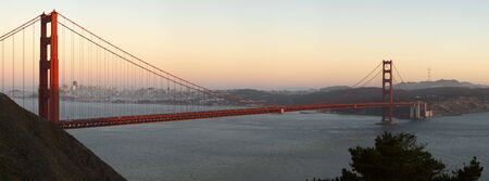 panoramics: Golden Gate Bridge (San Francisco, California) lit by the rays of setting sun against a backdrop of downtown and sky glowing with orange and red hues.