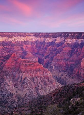 red wall: Red rays of setting sun color the walls of Great Canyon and tint clouds delicate pink at Bright Angel Viewpoint, North Rim. Image stitched from 3 frames.