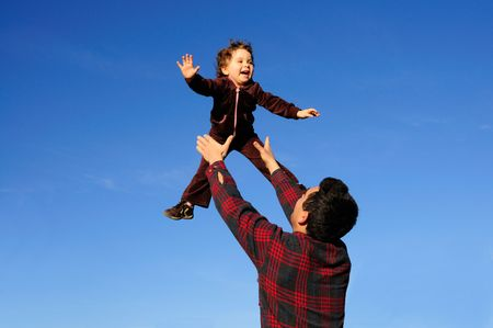 flying man: A happy two year old girl tossed into the blue sky by her father. Stock Photo