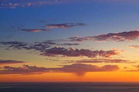 squall: Majestic sunset over Pacific Ocean with a silhouette of a lonely ship far off and a rain squall visible in the distance.
