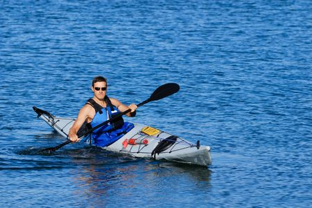 mastery: Athletic man showing off his mastery of sea kayak in blue calm waters of Mission Bay, San Diego, California.