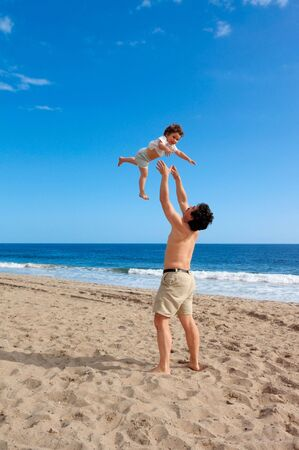 two and a half: A happy two and a half year old girl tossed into the air on a summer beach at Point Mugu State Park, California