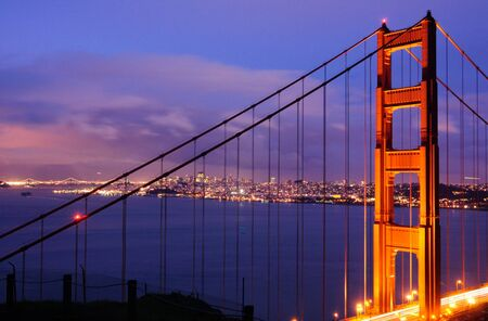 The North Tower of Golden Gate Bridge against the background of Bay Bridge and San Francisco skyline, shot from Battery Spencer (Marin Headlands) at dusk. Foto de archivo