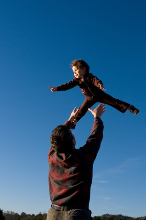 flying man: A two year old girl is pointing at something while being tossed up by her father.