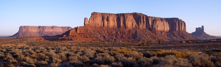barren: Dawn bathes Sentinel Mesa in warm light in Monument Valley, Navajo Nation.  Stock Photo