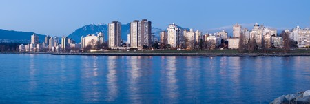 panoramics: High-rises at English Bay, Vancouver, Canada are lit by the last rays of setting sun. Stock Photo