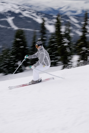 emphasizes: A young female skier rushs down the slope of a British Columbia mountain  Slow shutterand panning  produces motion blur  and emphasizes the sense of speed  Stock Photo