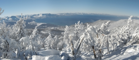 tahoe: A panoramic view of Lake Tahoe, shot from one of the mountain tops in the area shot on a very cold sunny winter day after a big snowstorm  Deep snow covers the land, pines and surrounding snowcapped mountains
