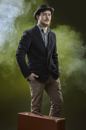 bowler hat: Victorian young man with beard and mustache in bowler hat. Dark green smoke background. Standing portrait.