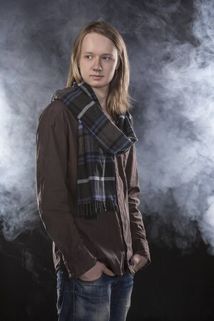 checkered scarf: Young man with long fair hair in checkered scarf. Dark blue smoke background. Standing portrait.