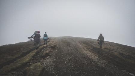 People walks on mountain road in dense fog